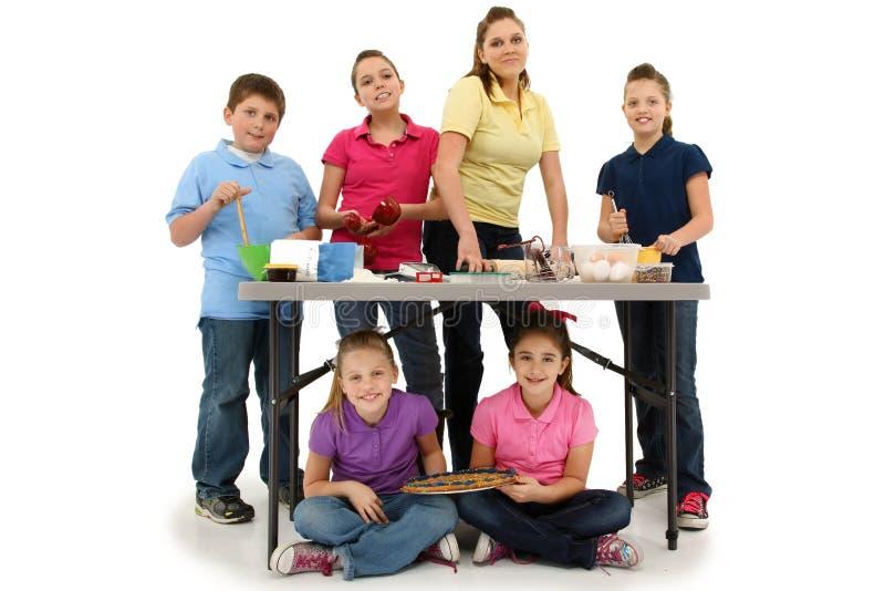 Sex syskon som tillsammans bakar kakor royaltyfri foto