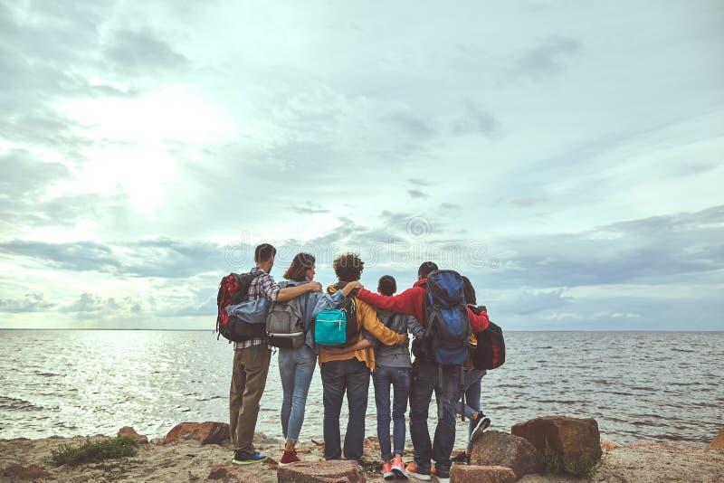 Sex vänner som omfamnar på havskusten royaltyfria bilder
