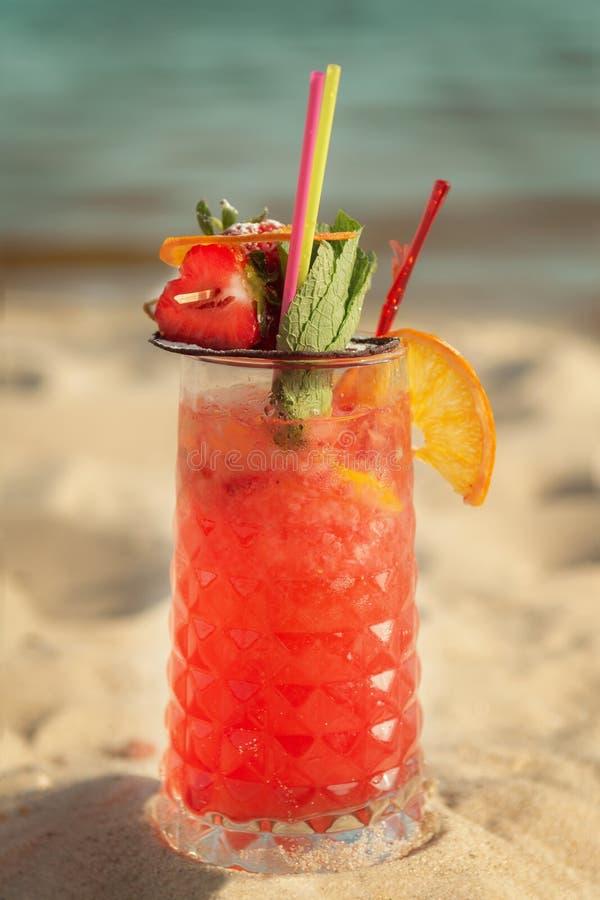 Sexe rouge de cocktail sur la plage contre la mer Tonalit? chaude image libre de droits