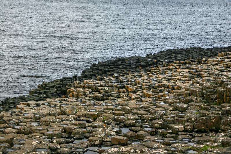 Sexhörningen formade stenar på stranden på jätte- vägbank, nordligt I royaltyfria foton