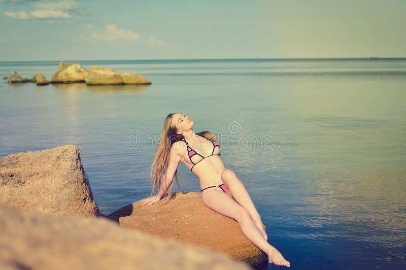 Sexi blond wijfje die op rots door overzees zonnebaden royalty-vrije stock foto's