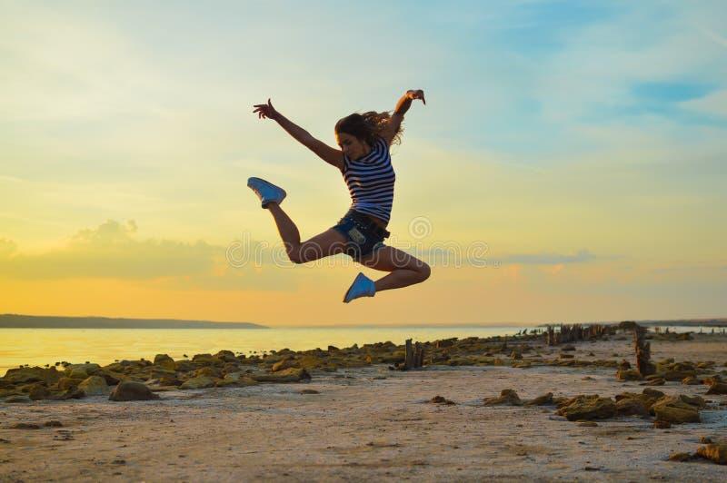 Sexi jong meisje die op hoogte in medio lucht springen bij stock fotografie
