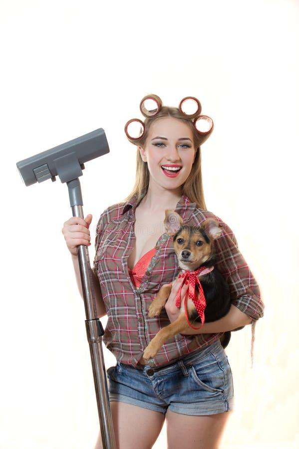 Sexi jonge blonde dame in krulspelden die van een hond houden stock foto's
