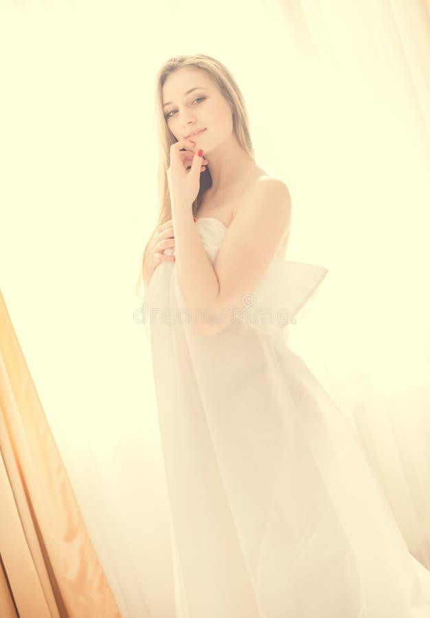 Sexi jonge mooie dame in witte status door venster royalty-vrije stock afbeelding