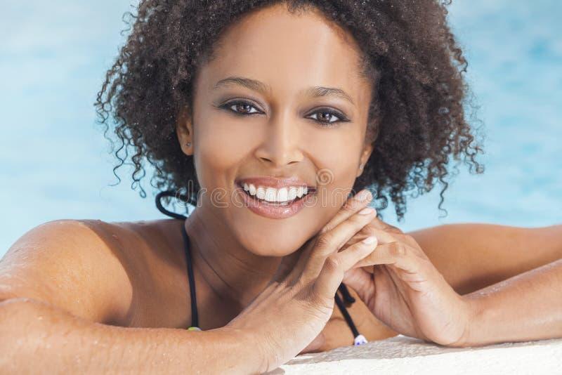 Sexig afrikansk amerikankvinnaflicka i simbassäng royaltyfri fotografi