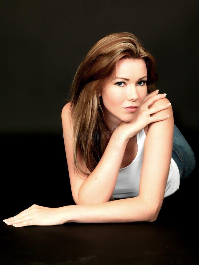 Sexig avkopplad sinnlig attraktiv ung kvinna som ligger på golv fotografering för bildbyråer