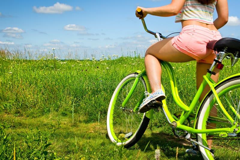 Sexig baksida för ung sexig kvinna på cykelkryssaren i natur arkivfoto
