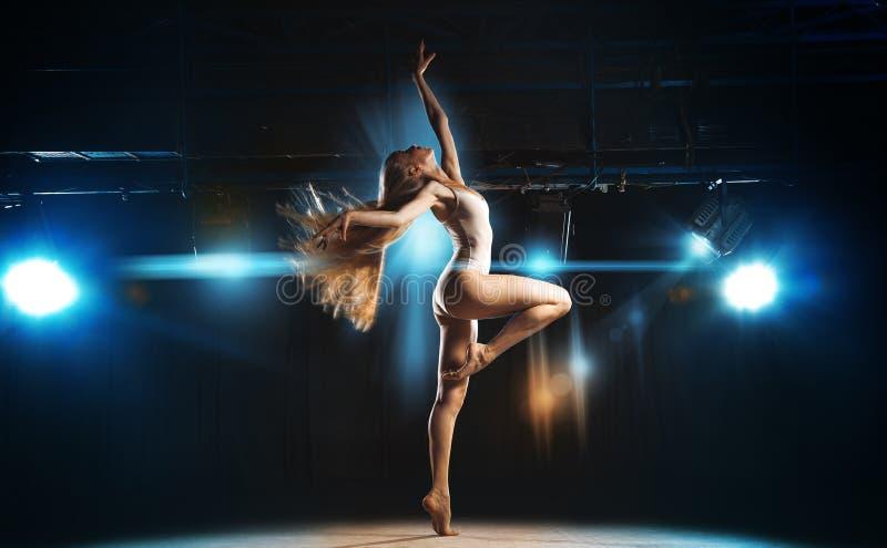 Sexig ballerina på etappen som poserar mot bakgrunden av spotlen arkivfoton