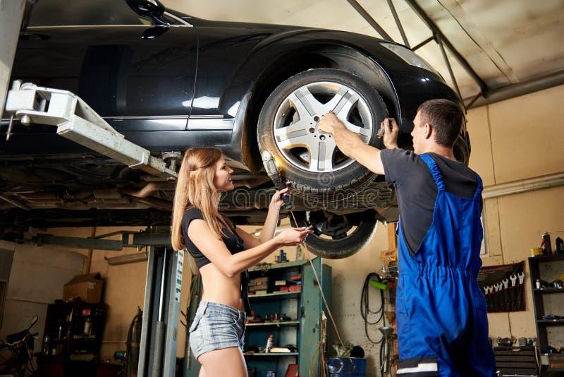 Sexig bil för reparation för auto mekaniker för kvinnahjälp på hydraulisk elevator royaltyfri fotografi