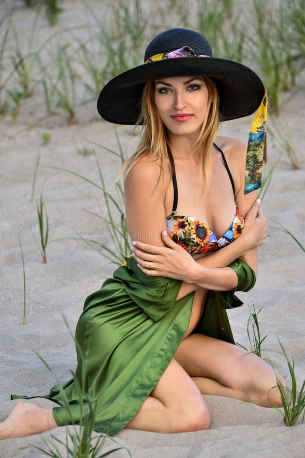 Sexig blond bikinimodell som poserar på stranden, den bärande färgrika baddräkten, den siden- skjortan och hatten fotografering för bildbyråer
