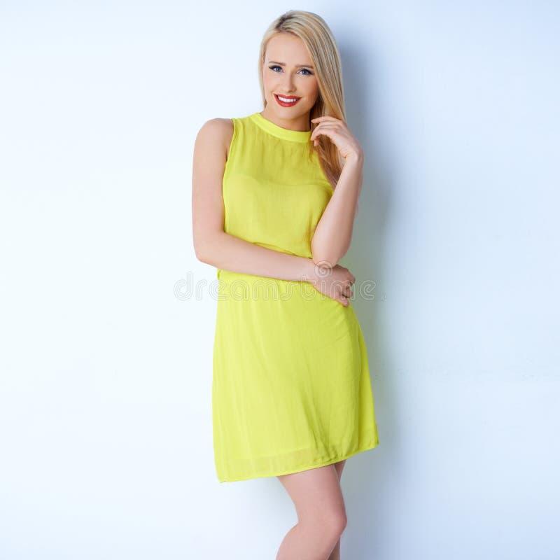 Sexig blond kvinna i gul klänning arkivfoto