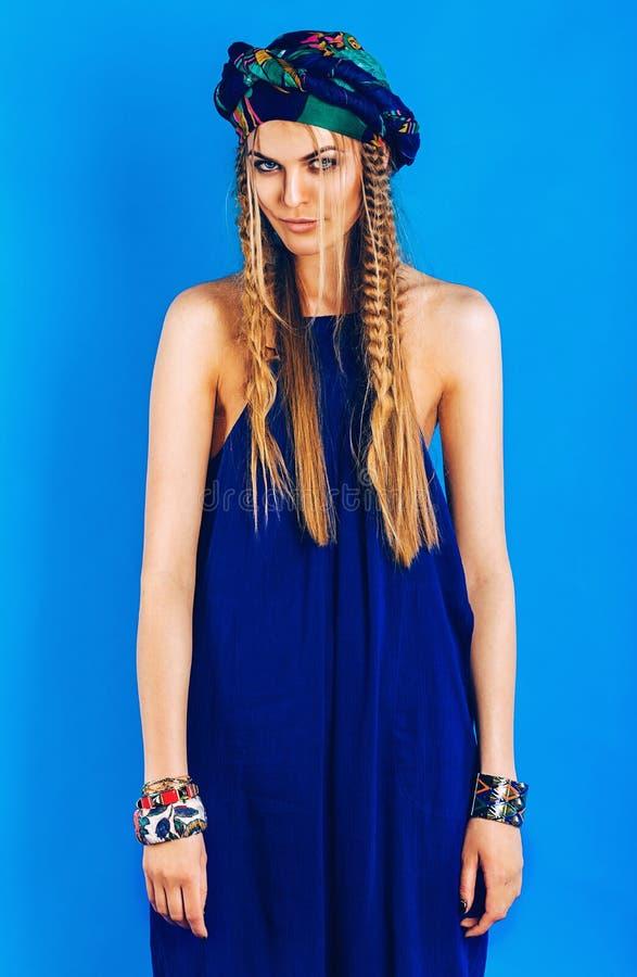 Sexig blond kvinna i ultramarine turban i overall arkivfoton