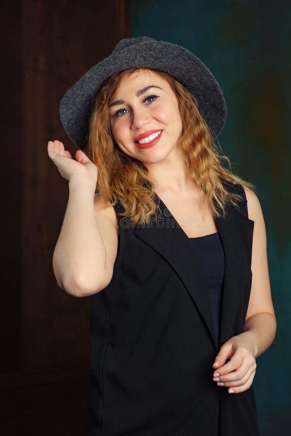Sexig blond kvinna med röda kanter i hatt inomhus arkivfoto