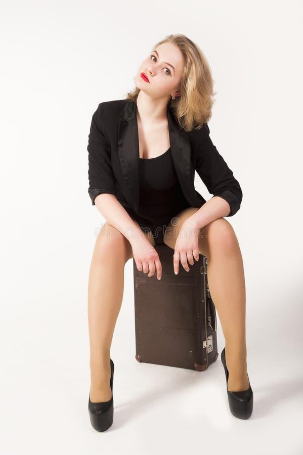Sexig blond kvinna på gammal resväska arkivfoton