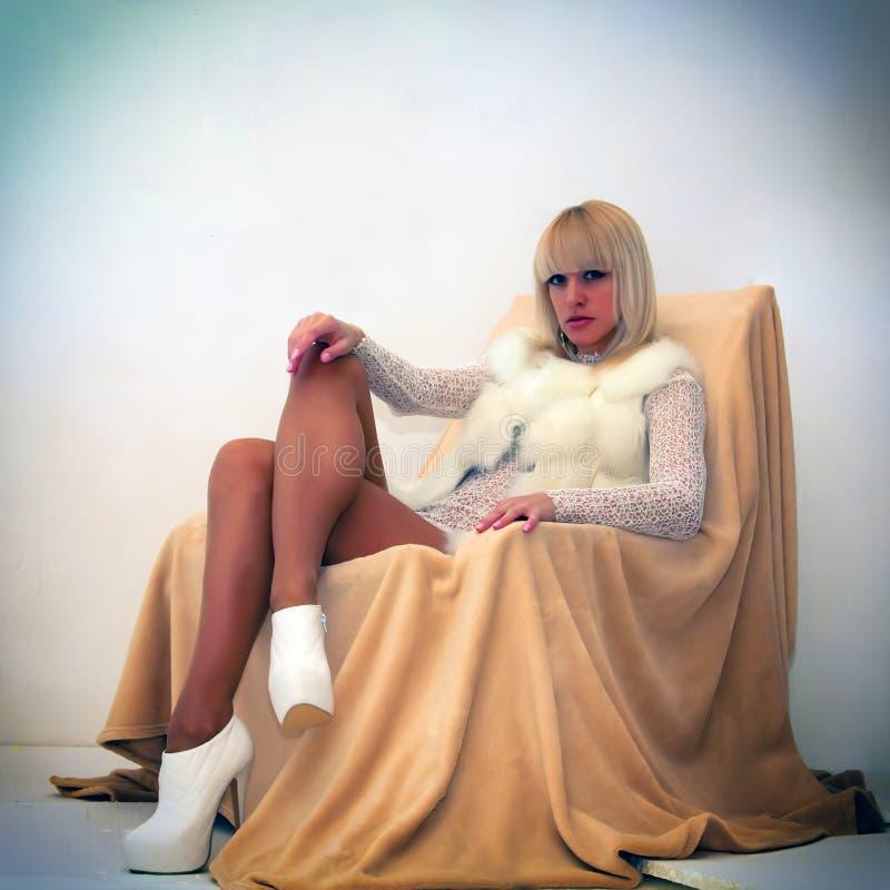 Sexig blond kvinna som ligger på fåtöljen arkivbilder