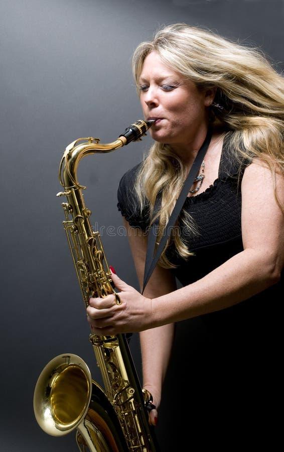 sexig blond saxofon för kvinnligmusikerspelare royaltyfria bilder