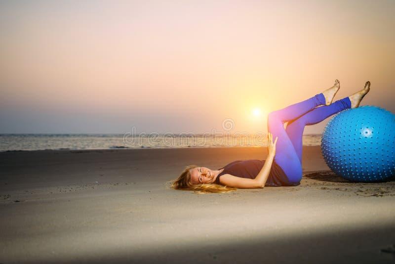Sexig blondin med konditionbollen på stranden utomhus Skönhet ligger på sanden i aftonljuset mot solnedgången över havet royaltyfri foto
