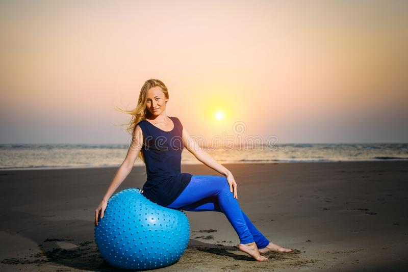 Sexig blondin med konditionbollen på stranden utomhus Skönhet sitter på en stor blå boll i aftonljuset mot solnedgång arkivfoto
