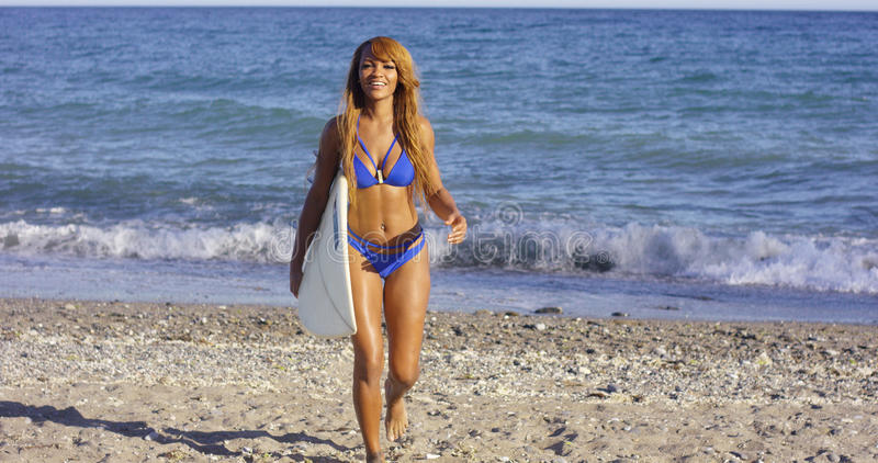 Sexig brunbränd kvinna som går med hennes surfingbräda royaltyfria foton