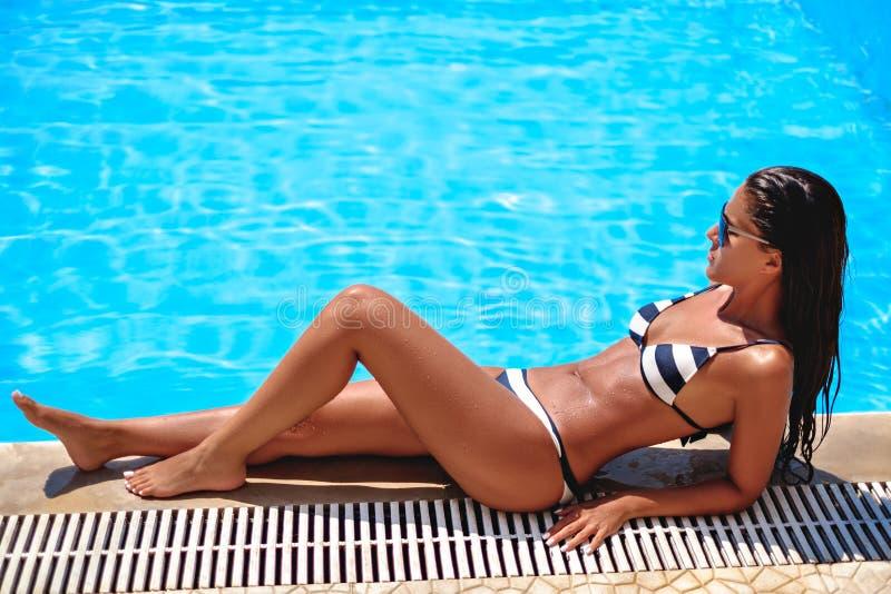Sexig brunbränd och våt flicka som ligger på simbassängkanten arkivbilder