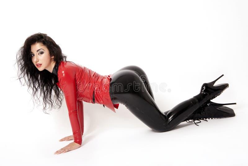 Sexig brunett i svart och röd latex. Kickhäl royaltyfria bilder