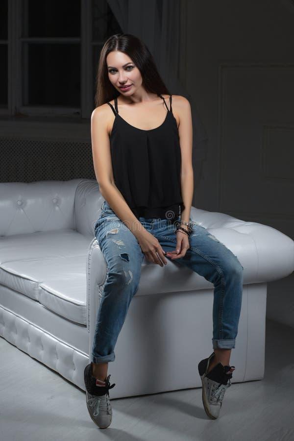 Sexig brunett som poserar att sitta på en soffa fotografering för bildbyråer