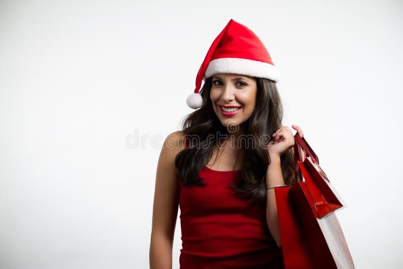 Sexig brunett som rymmer röda shoppingpåsar royaltyfria foton