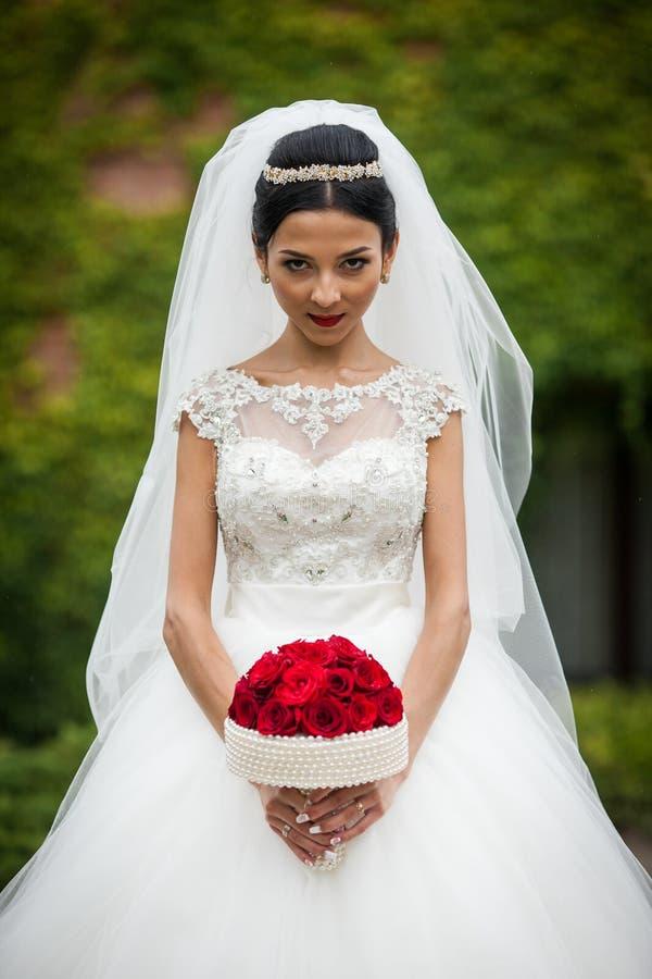 Sexig brunettbrud i stilfull vit klänning för tappning med den röda rosen fotografering för bildbyråer