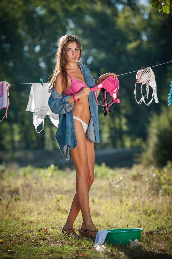 Sexig brunettkvinna i bikinin och skjortan som sätter kläder för att torka i sol Sinnlig ung kvinnlig med långa ben som ut sätter arkivbild