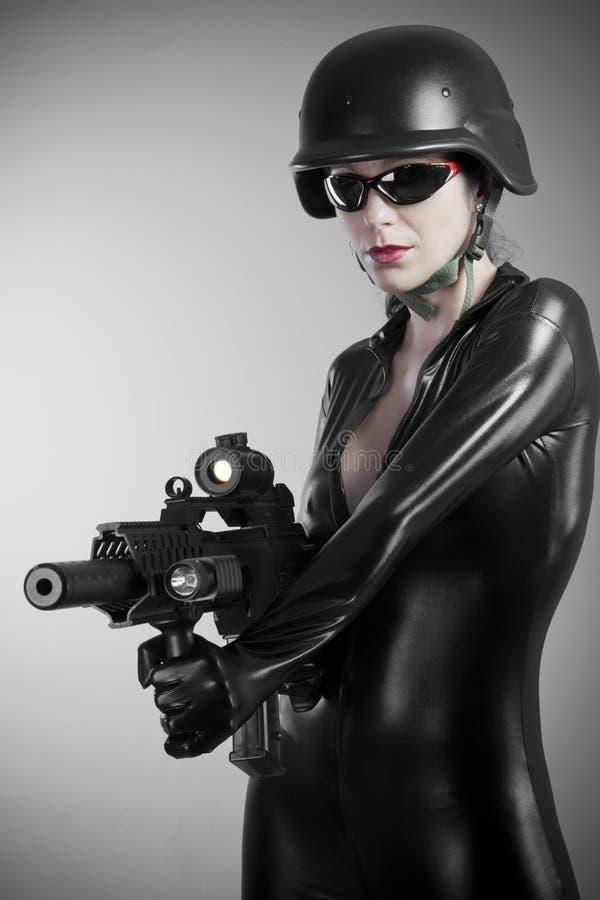 Sexig brunettkvinna i latexjumpsuit med den skurkrollvapnet och hjälmen royaltyfri foto