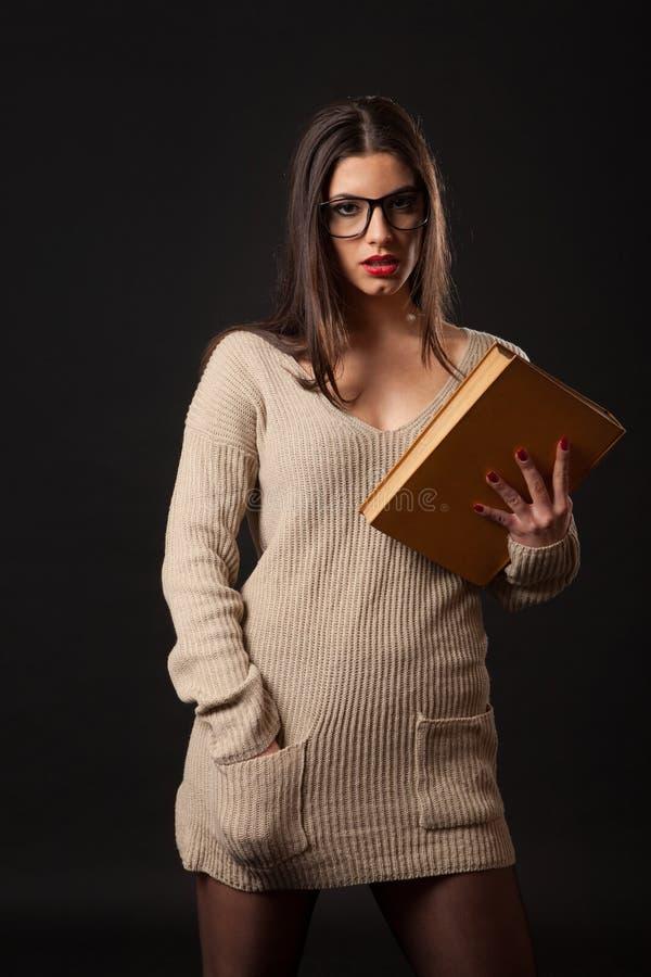 Sexig brunettkvinna med boken förestående arkivbilder