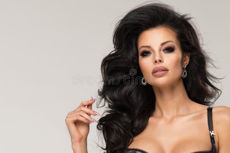 Sexig brunettkvinna som poserar i trendig damunderkläder i studio fotografering för bildbyråer