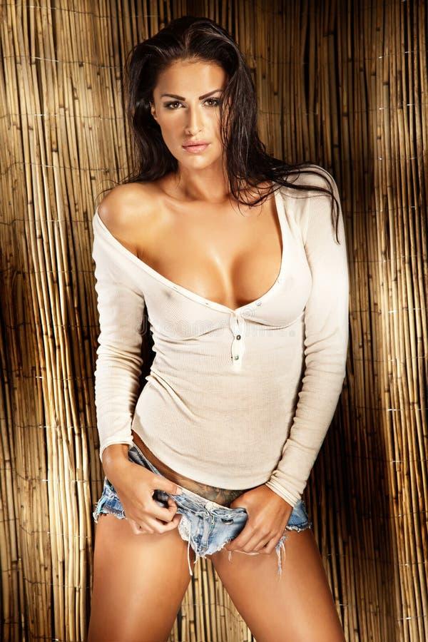 Sexig brunettlady, i att posera för vitskjorta royaltyfri bild