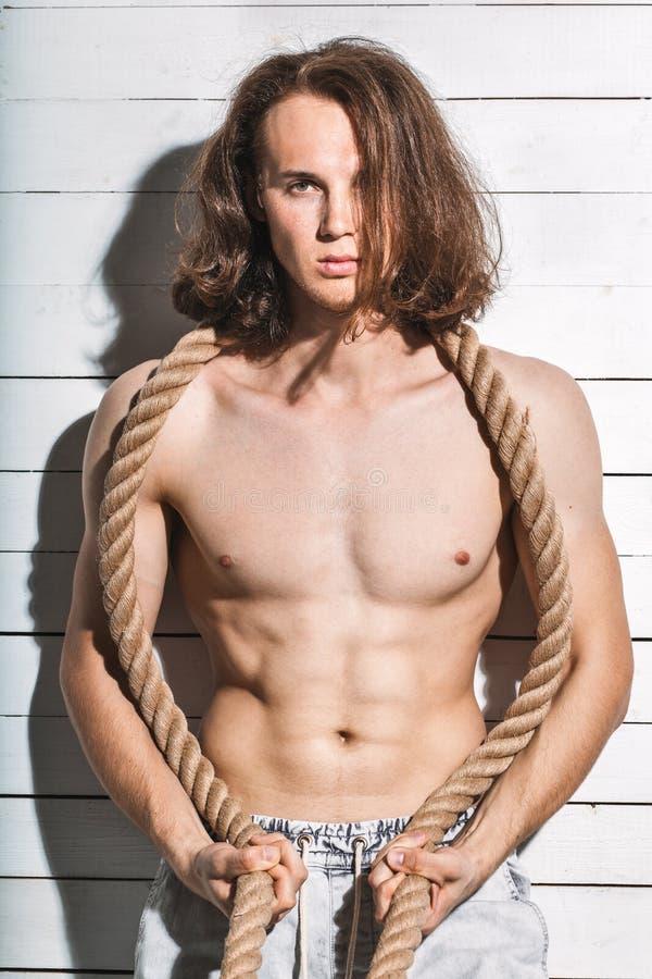 Sexig caucasian manmodell som är shirtless med repet på vit bakgrund arkivfoton
