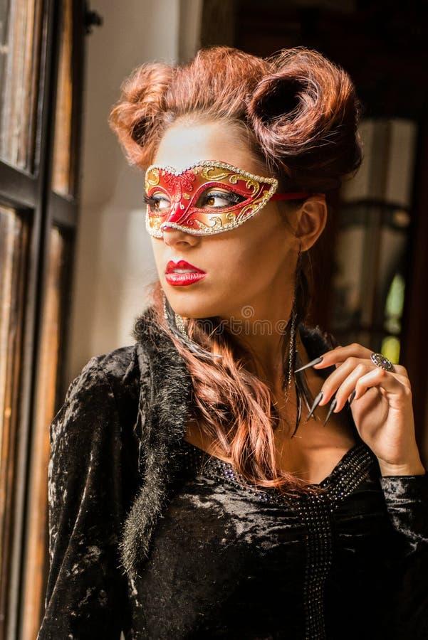 Sexig Caucasian modell med den röda maskeringen för karneval som ser till och med arkivfoton