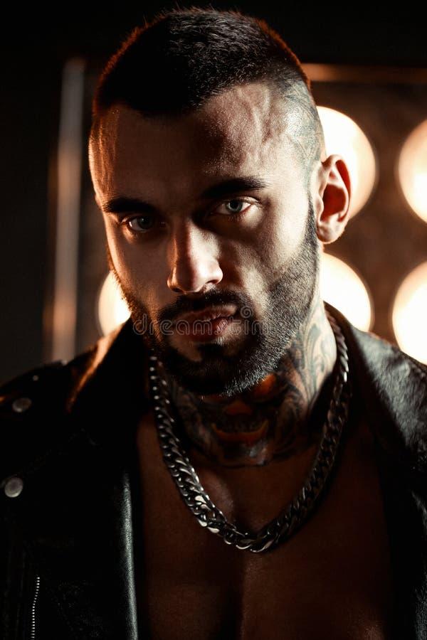Sexig closeupstående av den brutala stiliga manliga modellen i modeläderomslag och med ett svart skägg Tatueringskalle och royaltyfria foton
