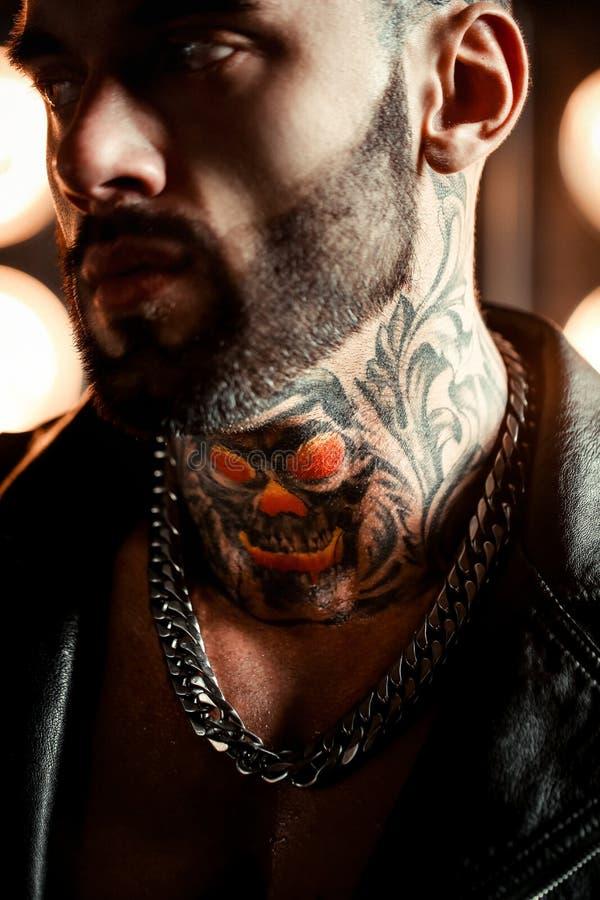 Sexig closeupstående av den brutala stiliga manliga modellen i modeläderomslag och med ett svart skägg Tatueringskalle och arkivfoton