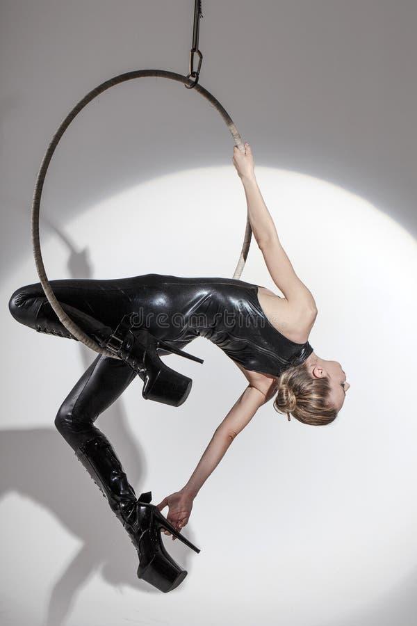 Sexig dansare i latexcatsuit på flyg- beslag royaltyfri fotografi