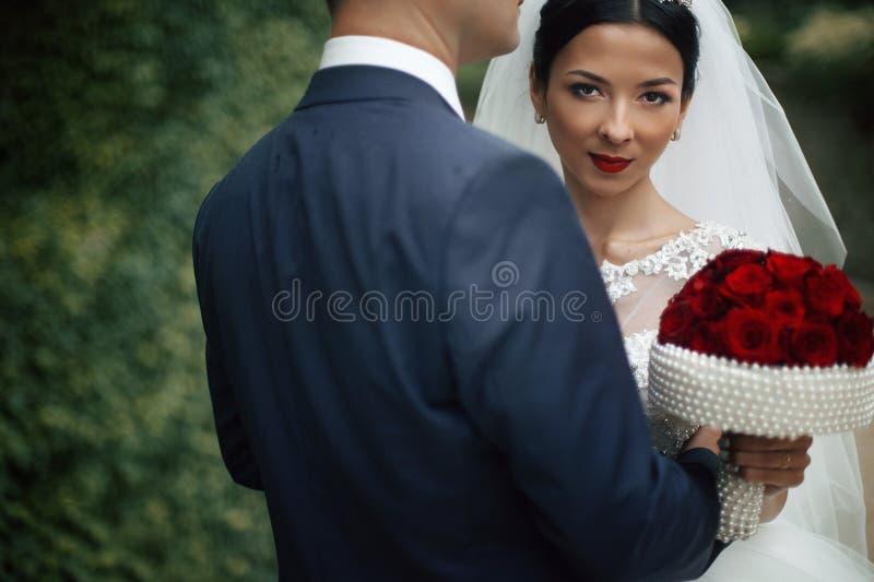 Sexig emotionell brunettbrud som kramar brudgum- och innehavbuketten royaltyfri bild