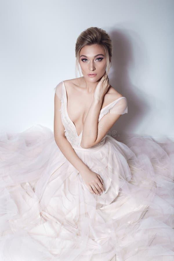 Sexig flicka för härlig delikat brud i mjuk rosa skazachnobröllopsklänning med ett snitt på bröstkorgen och baksidan med makeup-  royaltyfria bilder