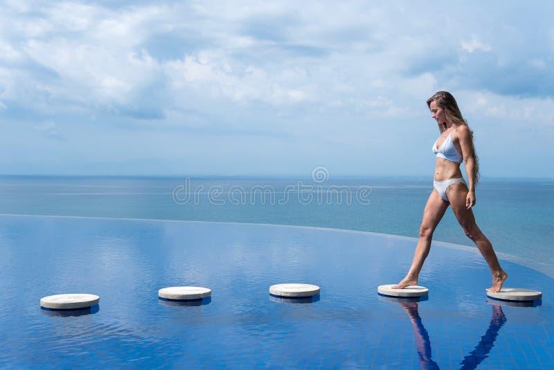 sexig flicka härlig kvinna underkläderna för modelldambikinin sitter kanten av vattenbadpölen på taket av hotellet för den lyxiga royaltyfri fotografi