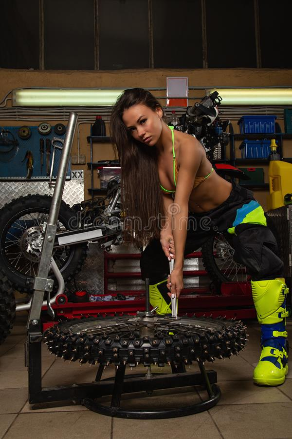 Sexig flicka i garage med cykelgummihjul royaltyfria bilder