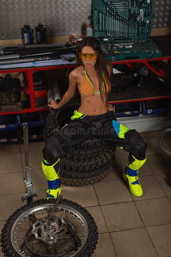Sexig flicka i garage med cykelgummihjul fotografering för bildbyråer