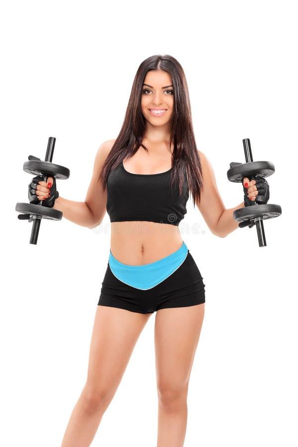 Sexig flicka i sportswear som övar med två skivstånger royaltyfri fotografi