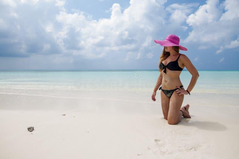 Sexig flicka i svart baddräkt, hatt och solglasögon på hans knä in arkivbilder