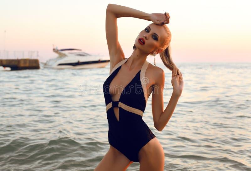 Sexig flicka med blont hår i baddräkten som poserar på stranden arkivfoto