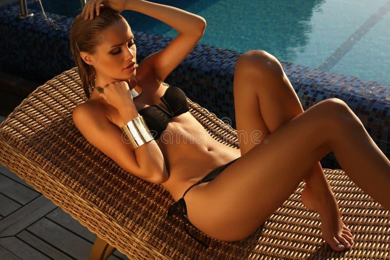 Sexig flicka med blont hår i bikini som kopplar av bredvid en simbassäng royaltyfri fotografi