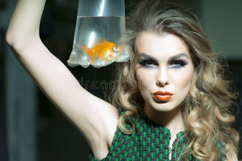 Sexig flicka med guldfisken arkivbild