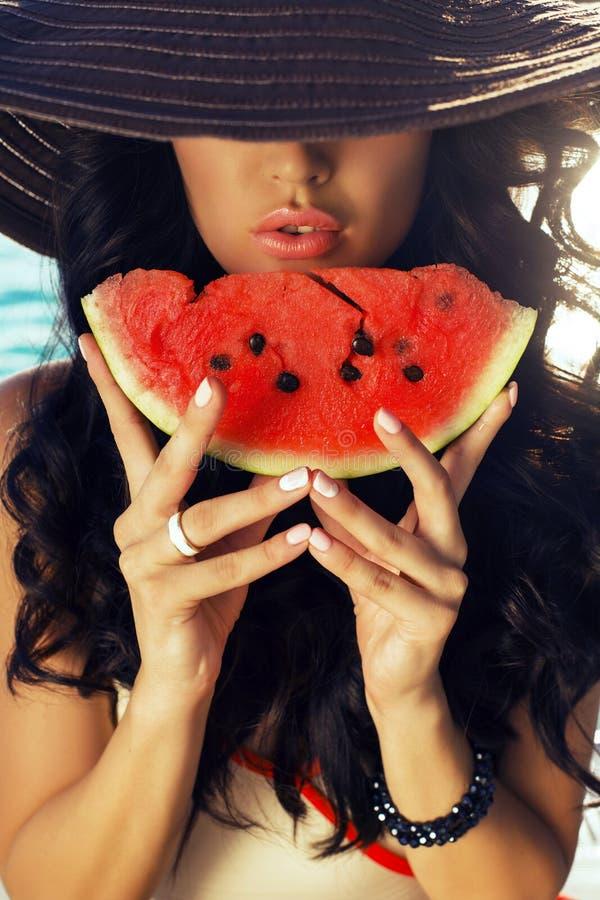Sexig flicka med mörkt hår som äter vattenmelon royaltyfri foto