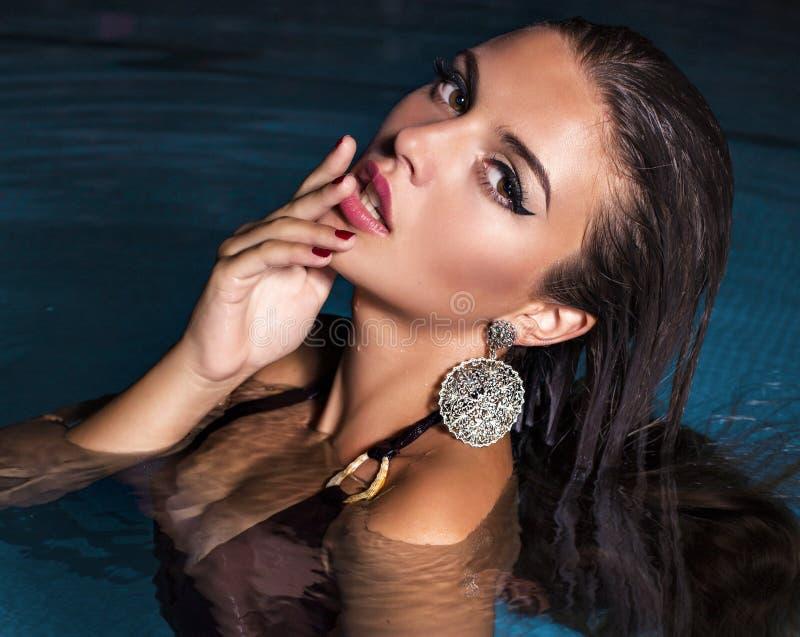 Sexig flicka med mörkt hår som poserar i simbassäng royaltyfria bilder